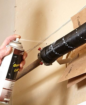 <b>Use a garage door lubricant</b></br> <p>Slide a piece of cardboard or paper grocery bag between the spring and the wall. Then saturate the spring with garage door lube spray. Wipe off the excess.</p>