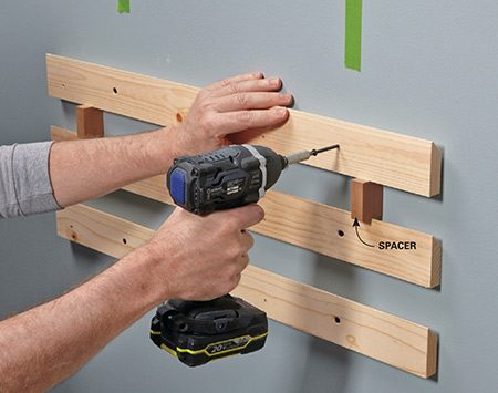 <b>Photo 5: Mount the wall cleats</b></br> <p>Mark the stud locations with tape and screw on the lowest cleat. Then work your way up the wall, using spacers to position each cleat.</p>