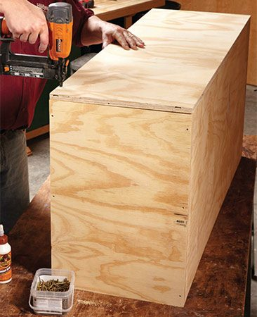 <b>Photo 3: Add the back</b></br> <p>Use the back to square up the cabinet. Fasten the whole length of one side, and then align the other sides with the back as you go.</p>