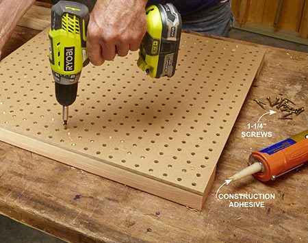 <b>Photo 3: Assemble the legs</b></br> <p>Drill five holes about 2 in. from the edge of the pegboard with the countersinking bit. Spread a bead of construction adhesive on the legs and attach the pegboard with 1-1/4-in. screws. If glue oozes through the holes, wait for it to dry. Then shave it off with a sharp chisel.</p>