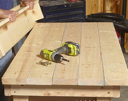 <b>Photo 7: Install the backboard</b></br> <p>Attach the 1x4 shelf to the 1x10 backboard. Then add a 2x4 block at each end. Rest the backboard assembly on the workbench and drive screws through the back to hold it in place.</p>