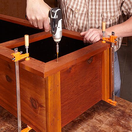 <b><b>Photo 6:</b> Secure the face frame</b></br> Clamp the face frame into place and hold it down with adhesive and trim-head screws. Leave the screw heads flush with the surface to avoid pockets where water can pool and penetrate the wood.