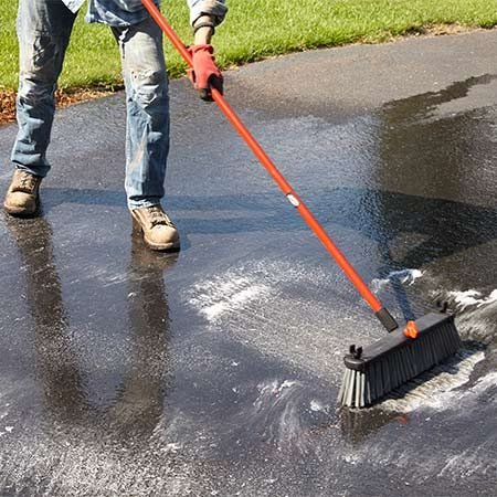 <b><b>Photo 1:</b> Soap and Scrub</b></br> Use the soap nozzle on your power washer or a garden hose applicator to apply the driveway cleaner. Then scrub the entire driveway with a stiff-bristle push broom.