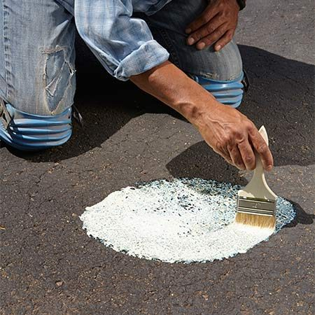 <b><b>Photo 3:</b> Pretreat the oil stains</b></br> Pour the oil spot primer on the damaged areas and brush it into the pores with a disposable chip brush. Apply a second coat to heavier stains. Let the primer dry fully before applying the driveway sealer.