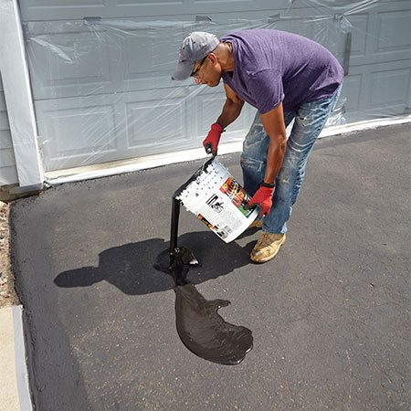 <b><b>Photo 7:</b> Pour onto the driveway</b></br> Start at the top left or right edge of the driveway and pour the sealer in an upside-down U-shape pattern.