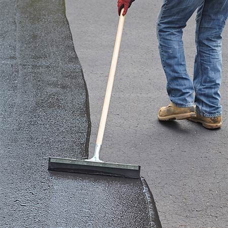 "<b><b>Photo 8:</b> Spread the sealer</b></br> Start at one leg of the upside down ""U"" and apply even pressure to spread the puddle across the driveway and down along the opposite leg. Then pick up the excess sealer on the down leg and start the next row."