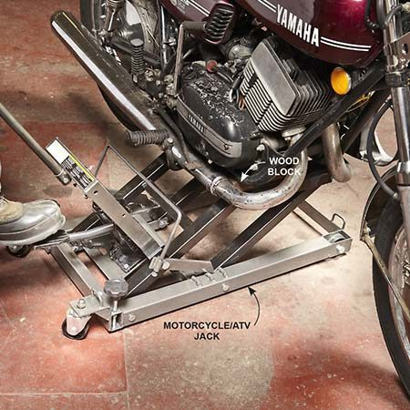 <b>Photo 2: Raise the bike</b></br> Roll a motorcycle jack under the bike and locate the jack pads so they contact the engine and transmission, not the exhaust pipes. If the pipes are in the way, place short wood blocks on the pads to increase clearance. Then jack up the bike.