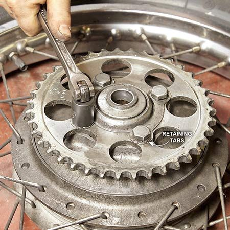 <b>Photo 6: Replace the sprockets</b></br> Bend the retaining tabs down and remove the sprocket bolts. Then swap in the new sprocket and tighten the bolts using a torque wrench. Bend the tabs up and against the bolt flats.