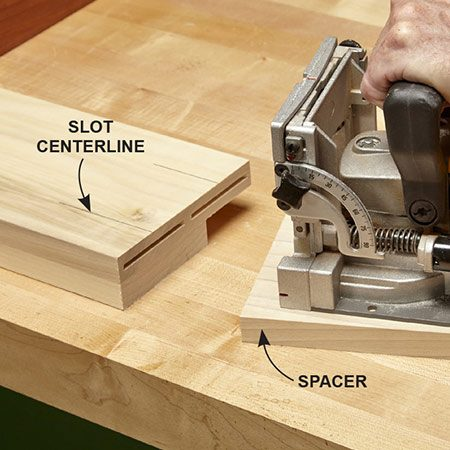 <b>Photo 4: Make slots in the guides.</b></br> <p>Cut biscuit slots in the side/guides, using the spacer again. This puts the drawer guides flush with the inside edge of the legs.</p>