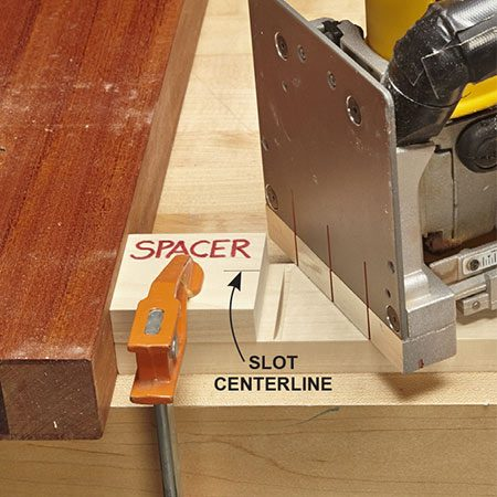 <b>Photo 5: Cut slots in stretchers</b></br> <p>Make vertical slots in the stretchers that go between the legs. Butt the plate joiner against a spacer to locate each slot.</p>