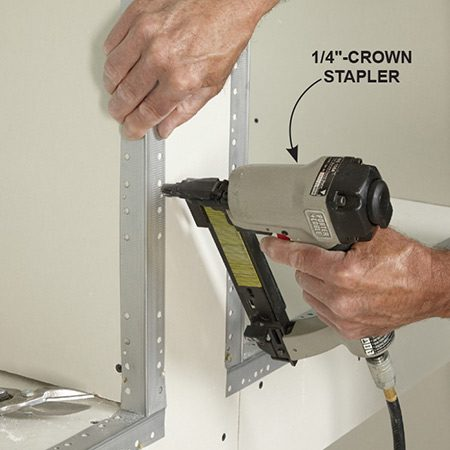 <b>Photo 12: Attach corner bead with a stapler</b></br> <p>Using a 1/4-in.-crown pneumatic stapler and 1-in.-long staples, drive staples every 6 in. and wherever the corner bead is buckled out. Then cover the edge of the bead with mesh tape.</p>