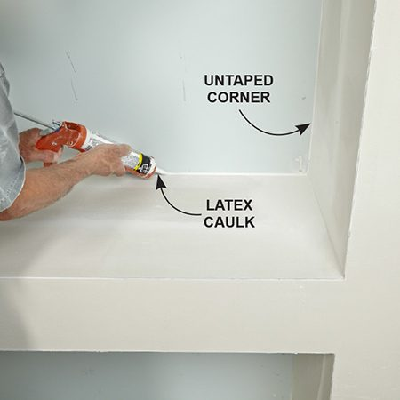 <b>Photo 15: Caulk the back corners</b></br> <p>Avoid a lot of tricky corner taping by caulking the back inside corners. Cut the tip of the latex caulk tube carefully to create a very small hole. Then apply a neat bead of caulk and smooth it out with your finger.</p>