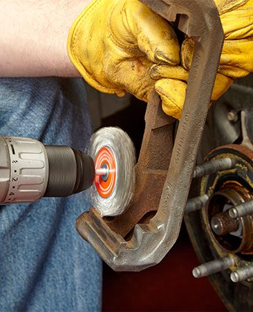 <b>Photo 5: Clean off the rust</b></br> <p>Toss the old anti-rattle clips (see Photo 1). Remove all traces of surface rust in the pad slide areas using a wire brush or a drill with a wire wheel. Coat the areas with a light film of brake grease. Install new anti-rattle clips.</p>