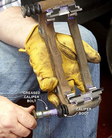 <b>Photo 7: Lube and install new boots</b></br> <p>Apply a coat of high-temperature synthetic brake grease to the bolt and the bores in the caliper bracket. Seat new boots into the caliper bracket and slide in the greased caliper bolts until the boots seat on the bolt recess.</p>
