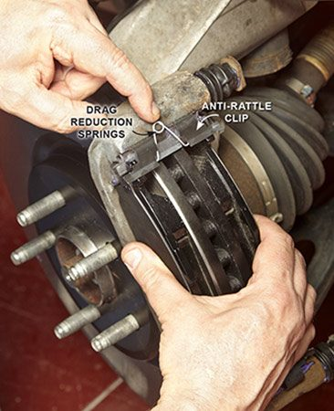 <b>Photo 10: Add the springs</b></br> <p>Slide the pads into the anti-rattle clips. Squeeze the pads together as you install the drag reduction springs. Make sure they go back in the same way they came out. Continue squeezing the pads and slide the caliper over the pads.</p>