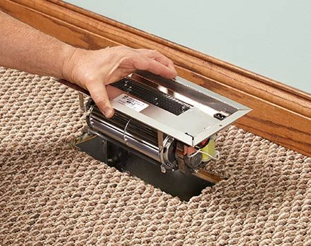 <b>Photo 1: Install the fan</b></br> <p>If the duct is a standard size, remove the register and drop the fan into the boot. Secure it to the floor on each side with screws. If the duct is smaller than standard, see photos below.</p>