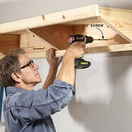 <b>Photo 4: Secure the shelf to the wall</b></br> <p>Use 4-in. lag or construction screws to secure the 1x8 back rim to the wall studs. Drive two screws into each stud—one high, one low.</p>