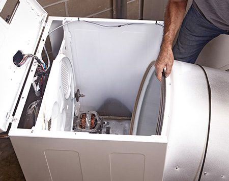 <b>Photo 1: Remove the drum</b></br> <p>Pop the lid and remove the front panel. Then disconnect the drive belt from the motor and lift the drum out the front of the machine.</p>