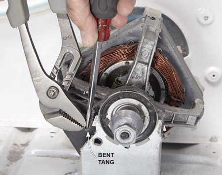 <b>Photo 3: Release the motor clamps</b></br> <p>Grab the bent tang on the motor clamp with slip-joint pliers. Then jam a flat-blade screwdriver between the clamp and the plier jaws and pry the clamp outward until it pops off. Repeat on the opposite end.</p>