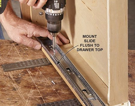 """<b>Photo 2: Install the tray slides</b></br> <p>Secure full-extension drawer slides to the top inside edges of the drawer. Install them """"backward"""" so they extend toward the back of the drawer. It's OK if they run an inch or so beyond the back of the drawer; most cabinets have extra space in back.</p>"""