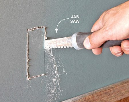 <b>Photo 2: Cut a hole for the new box</b></br> Trace the outline of the box on the wall at the same height as the existing box, and cut out the drywall with a jab saw. Keep the hole an inch or more away from any studs.