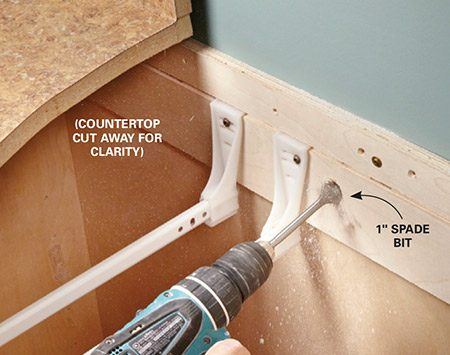 <b>Photo 3: Drill holes for the cable</b></br> Drill 1-in. holes through the back of the cabinet and drywall. Beware of hidden cable, ducts and pipes; when the bit breaks through the drywall, stop.