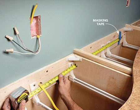 <b>Photo 5: Measure for the conduit length</b></br> Stick your tape measure through the conduit holes and secure it in the hole in the wall. Have a helper hold the end of the tape, or secure it with masking tape.