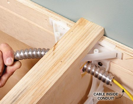 <b>Photo 6: Slide the conduit into place</b></br> Feed the new cable through the conduit, and then push the conduit through the 1-in. holes drilled into the sides of the cabinet.