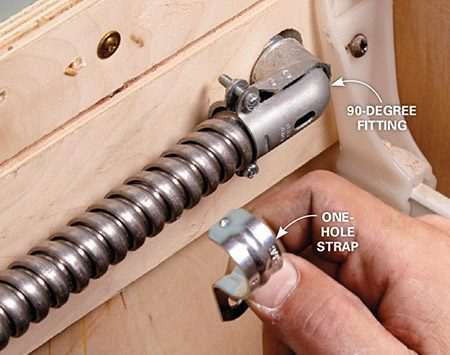 <b>Photo 7: Secure the conduit</b></br> Hold the conduit in place with straps. Place straps near the 90-degree fittings and one more in the middle if the conduit travels more than halfway across the length of the cabinet.