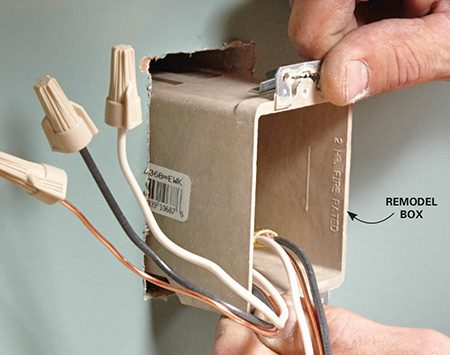 <b>Photo 8: Install the new boxes</b></br> Cut the sheathing off the cable before pulling the wires through the remodel boxes. Slide the boxes into the holes and fasten them to the drywall.