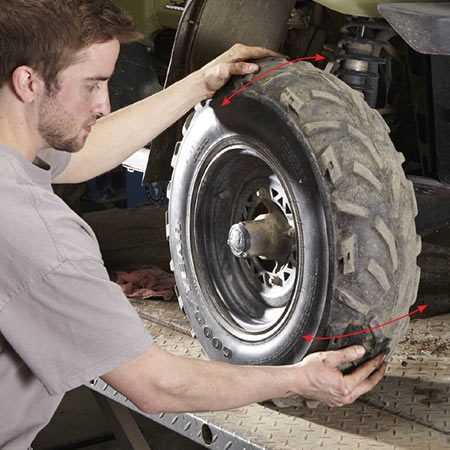 <b>Rock the tire in and out</b></br> Jack up one side and grab the tire at the 12:00 and 5:00 positions. Then rock the tire in and out. If you feel any play, you're looking at a bad wheel bearing, a bad ball joint or both.