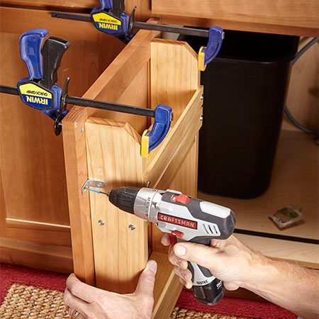 <b>Photo 3: Mount the rack</b></br> Center the rack on the door and drill screw holes. Wrap tape around the drill bit to act as a depth guide so you don't drill through the door. Clamps aren't absolutely necessary for this step, but they're a big help.