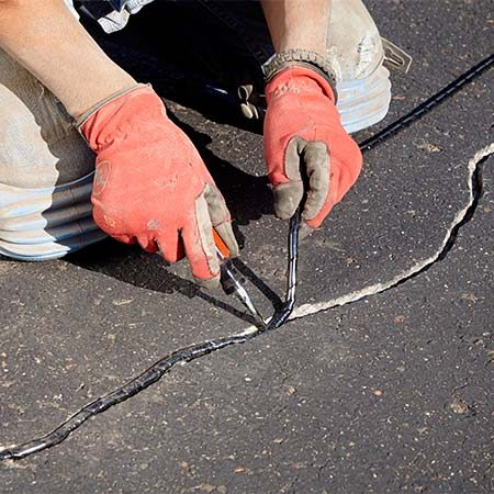 <b>Photo 2: Stuff the crack with filler</b></br> <p>Jam the filler deep into the crack using a flat-blade screwdriver. Add a second layer to fill deeper or wider cracks.</p>