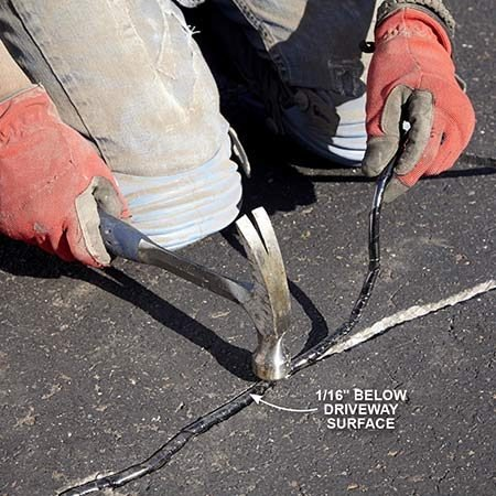 <b>Photo 3: Compress the filler</b></br> <p>Hammer the filler so it sits at least 1/16 in. below the surface of the driveway. Don't overfill.</p>