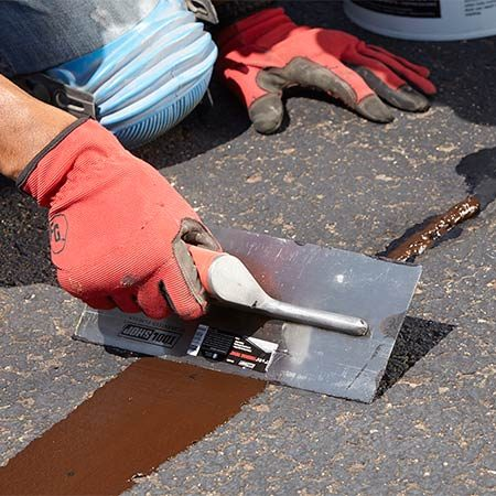 <b>Photo 5: Add trowel mix and then smooth it</b></br> After the filler has cooled, scoop up the trowel patch and tap it onto the crack filler to create a small mound. Smooth it with a trowel and let dry overnight. If a depression remains the next day, apply a second coat.