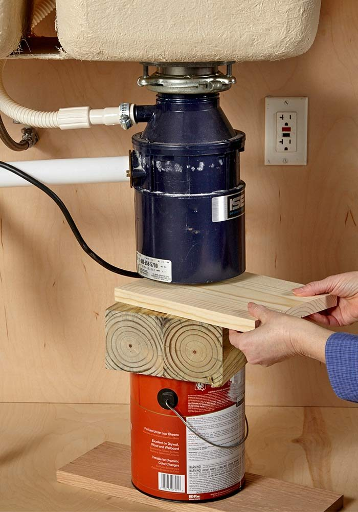 <b>Assemble a support</b></br> <p>Garbage disposals can weigh 15 lbs. or more. That's a lot of weight to suddenly catch with one hand while you're turning the lower mounting bracket with the other hand.</p>  <p>Before you unhook anything, assemble a support under the unit using a paint can and scraps of wood. Leave a 1/4-in. to 1/2-in. gap under the unit so it can drop a bit. Use the same support to help you install the new disposal.</p>