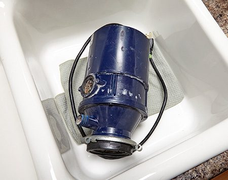 <b>Prevent shifting</b></br> After you install the new sink flange, you don't want it shifting around when you're assembling the parts underneath. Movement of the flange could break the seal between the flange and the sink, inviting a leak. Your best bet is to ask a helper to press down on the sink flange, or if you're working alone, find something to weight it down, such as the old disposal. Place an old towel under the weight so you don't scratch the sink. If the bottom of your sink is quite concave, the old disposal might not contact the flange. In that case, place a can on the flange, then weight down the can.