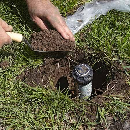 <b>Photo 1: Scoop out the dirt</b></br> Slice the garden spade straight down the sides of the hole to give you room to maneuver. Then lift the dirt up, out and onto the poly sheeting.