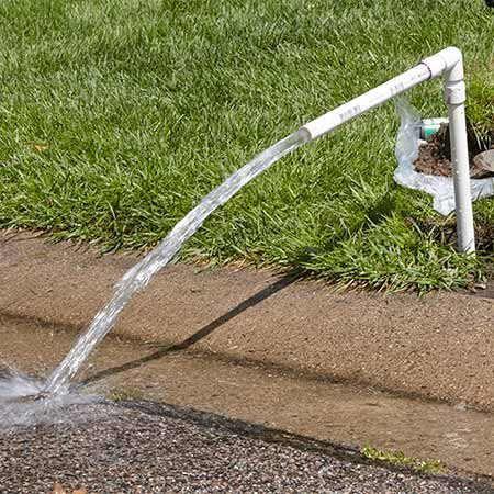 <b>Photo 3: Flush the line</b></br> Screw the flushing tool into the water line and aim it into the street or away from your work area. Turn on the water for that zone and let it run for about 30 seconds.