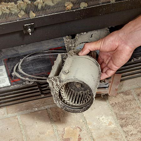 <b>Photo 3: Slide out the old blower</b></br> Pull the blower toward the front of the fireplace. Then rotate it so it clears the grille opening. If you need more clearance, remove the rubber feet.