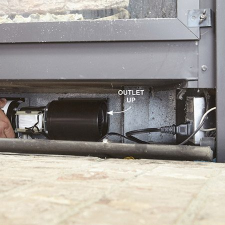 <b>Photo 4: Position the new blower</b></br> Roll the blower through the grille area and position it with the blower outlet pointing up. Push it all the way to the back of the fireplace until it contacts the back wall. Then pull it forward 1/4 in. to prevent vibration noise.