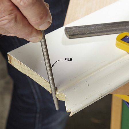 <b>Photo 3: Fine-tune the cope</b></br> Your coping cut doesn't have to be perfect. Even the best trim carpenters use files, rasps and sandpaper to clean up their cope cuts. Tight curves, for example, are almost impossible to cut with a coping saw. But a small file rounds them easily.