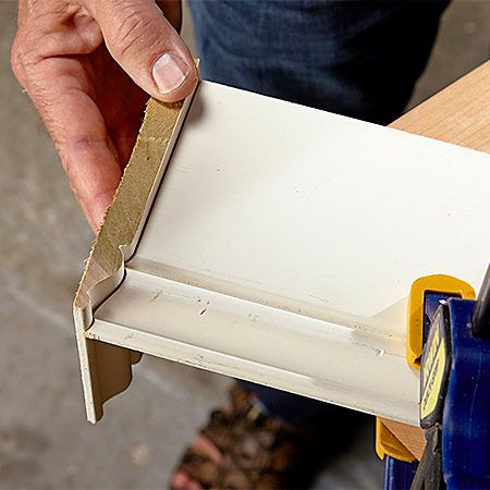 <b>Photo 4: Test the fit</b></br> Keep a scrap of the trim handy so you can check the fit as you fine-tune the cope. With really complex profiles, you may have to check and fine-tune the fit a dozen times before you get it right.