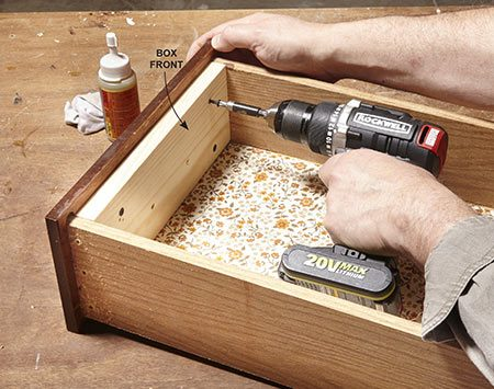 <b>Photo 2: Reinforce the drawer front</b></br> Drill four 1/8-in. pilot holes through the newly installed box front. Then drive coarse-thread drywall screws through the new box front and into the old drawer front.
