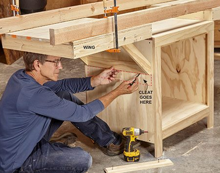 <b>Photo 8: Position the cleats</b></br> Secure the wings in the raised position using straight 2x4s and clamps, then mark the bottoms of the brackets. Position your cleats 1/4 in. above this mark.