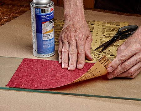 <b>Photo 1: Glue sandpaper to glass</b></br> Prepare your sharpening surface by spraying adhesive on the back of a sheet of 80-grit sandpaper. Stick the sandpaper onto a piece of 1/4-in. glass. Add 150 and 220 grit, too.