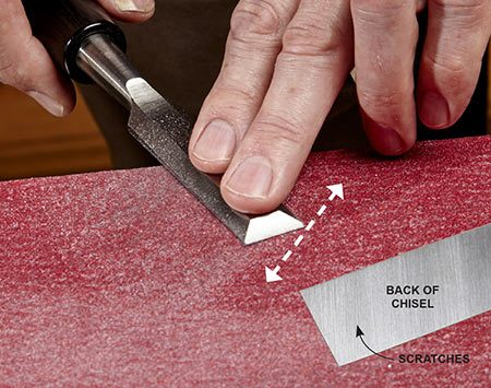 <b>Photo 2: Flatten the back</b></br> Rub the back of the chisel on the 80-grit paper until the first 2 in. are covered with scratches (see inset). Repeat with finer grits, rubbing in different directions so you can track your progress. You only have to do this once on a chisel.