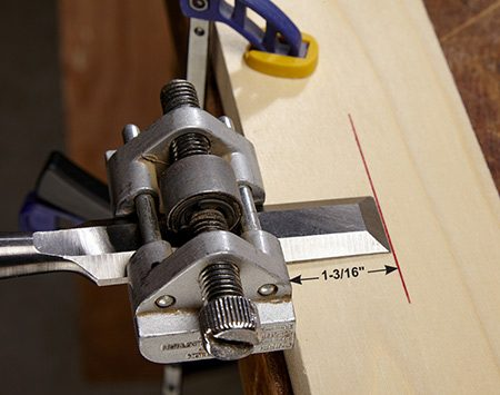 <b>Photo 3: Set the honing angle</b></br> The fastest way to get a really sharp edge is to use a honing guide. Clamp the chisel so it projects 1-3/16 in. from this type of guide; this will produce a 30-degree angle.