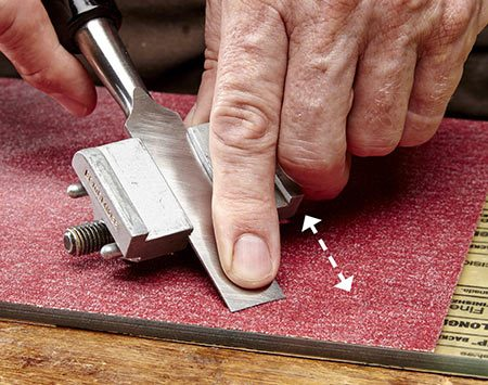 <b>Photo 4: Sharpen on sandpaper</b></br> Roll the honing guide on the 80-grit sandpaper to sharpen the chisel. You don't need oil or water for lubrication.