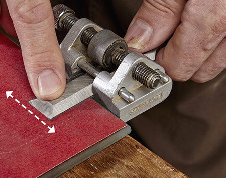 <b>Photo 6: Remove the wire edge</b></br> Rub the back of the chisel on the 220-grit paper to remove the wire edge. To produce an even sharper edge, repeat the honing process on 150- and 220-grit paper.